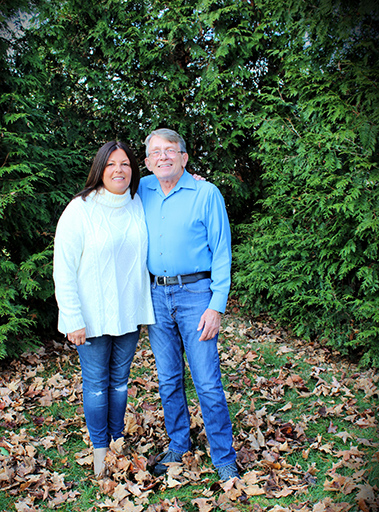 Skip and Susanne standing in front of evergreen trees