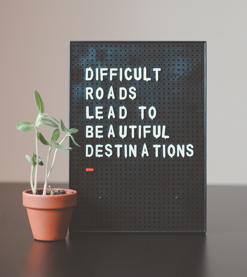 difficult roads lead to beautiful destinations on a menu board sitting next to a plant